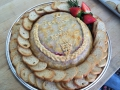Delicious baked Brie Cheese in puff pastry with raspberry sauce & crostinis